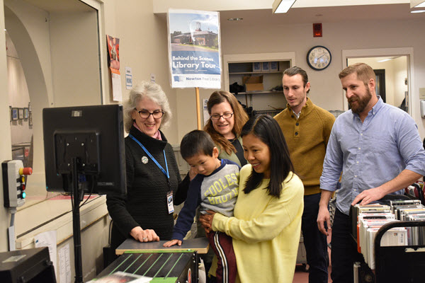 Newton library staff and patrons watch as child places book in automated sorter.