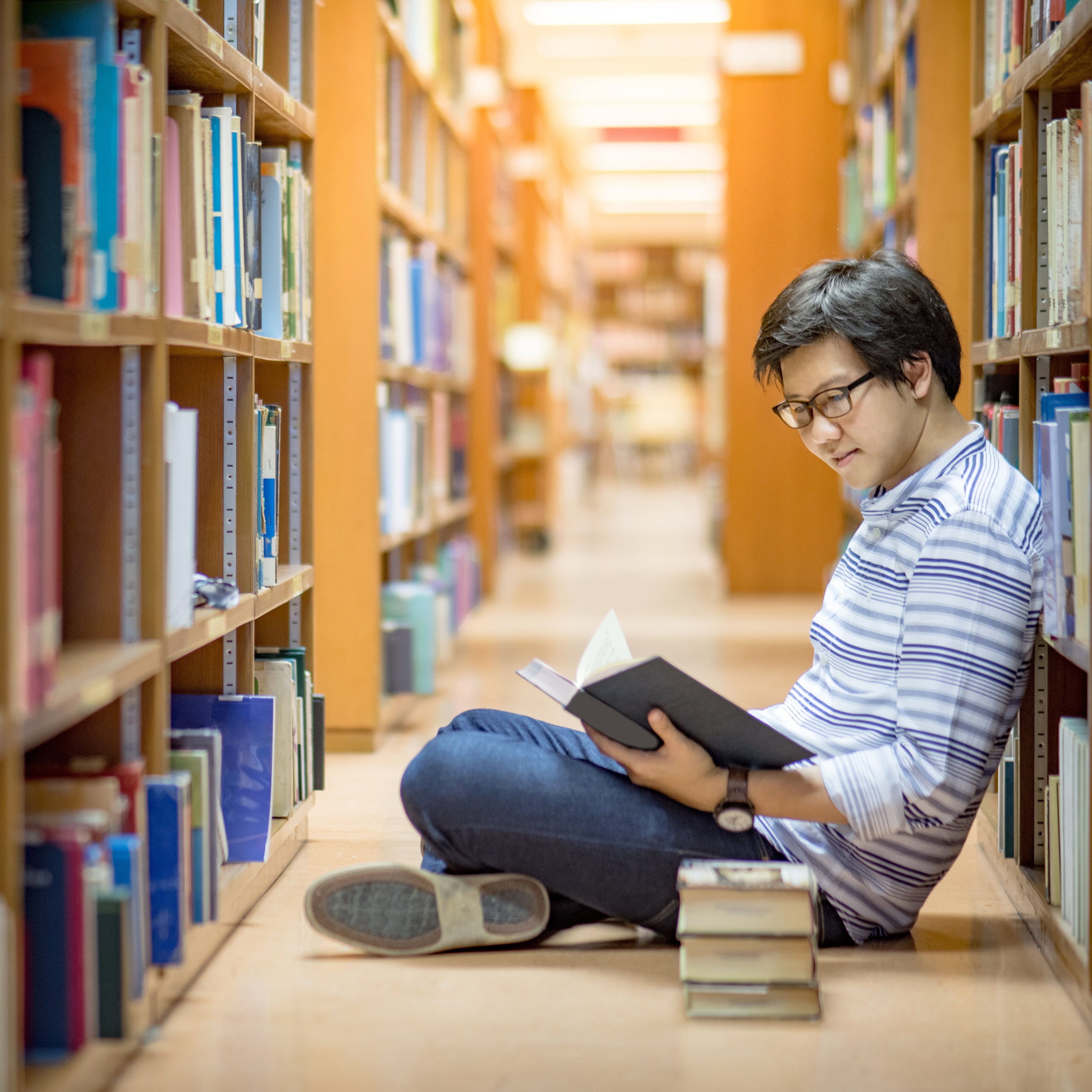 Young man reading in library stacks
